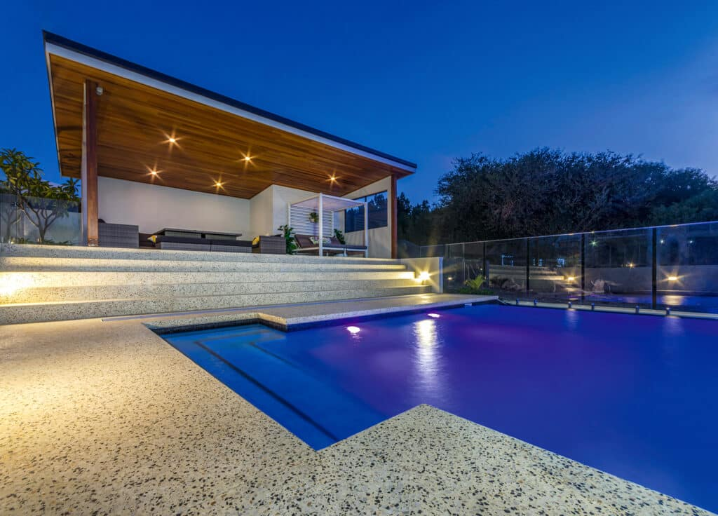 Honed concrete alfresco living area overlooking seamless concrete edge pool
