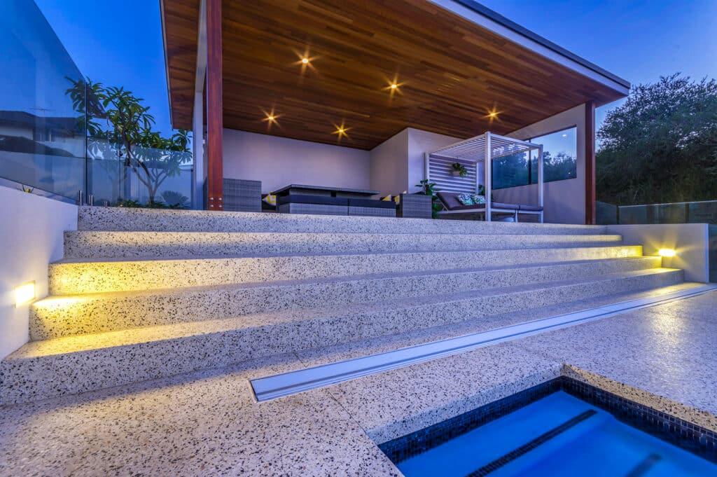 Honed concrete alfresco living area overlooking seamless concrete edge pool