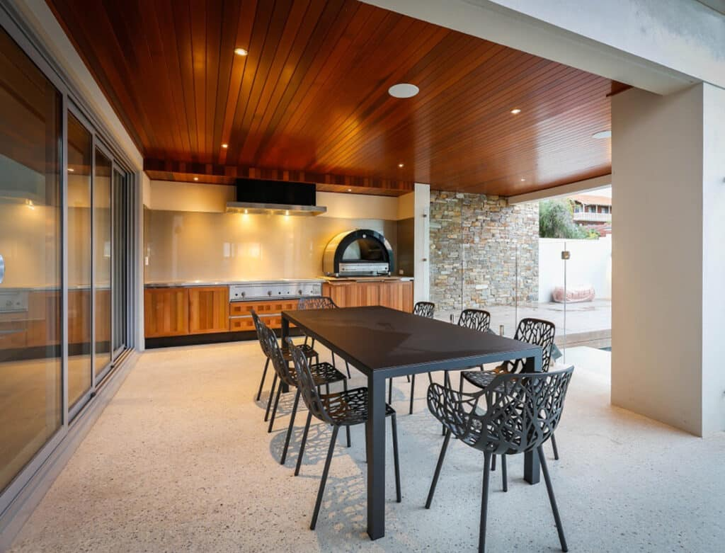 Outdoor alfresco kitchen and dining area with honed concrete floor