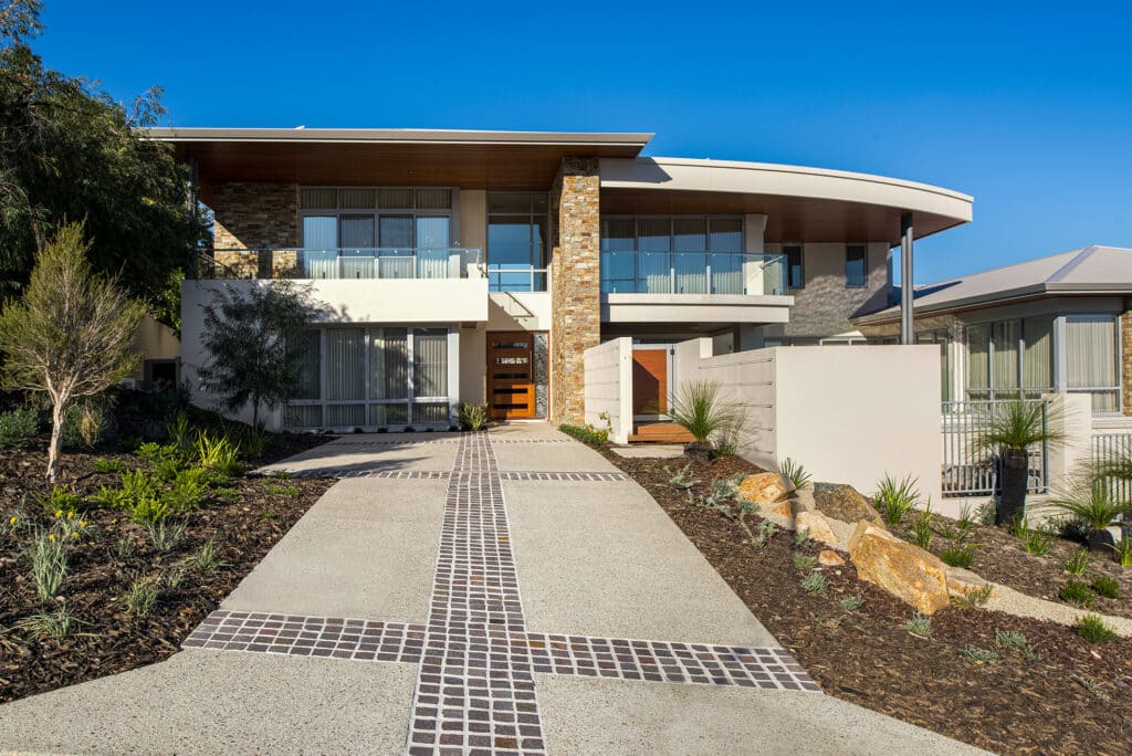 City beach home with exposed aggregate driveway with tiled stone inlays